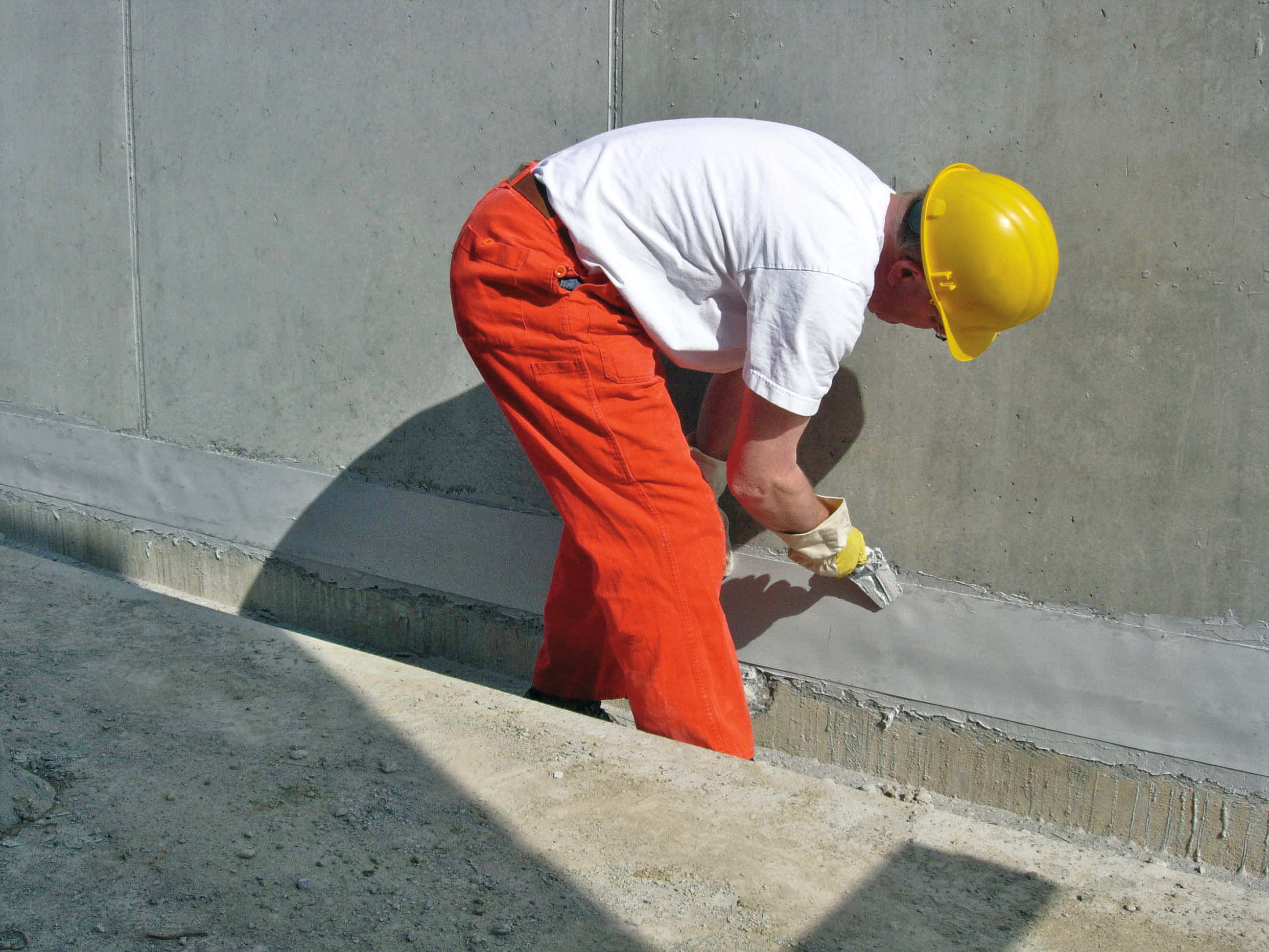 Male applicator applying Sikadur Combiflex to joint in concrete facade of building with hand trowel